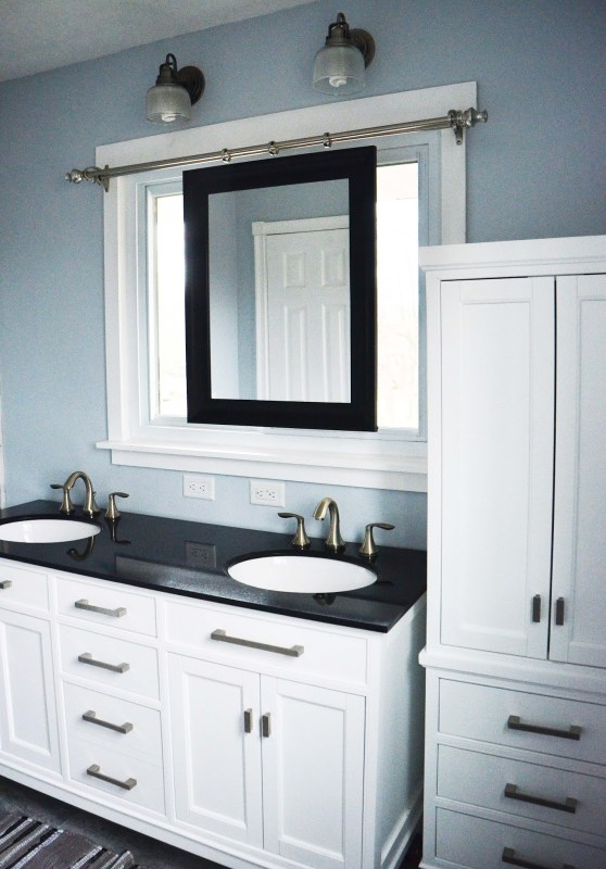 Beautiful master bathroom renovation, white with dark countertops, and a smart sliding mirror over the window above the sink
