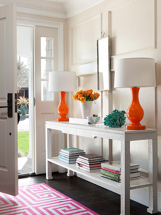 Neutral walls and furnishings but still so much COLOR in this entryway. Those orange lamps are awesome! | 100+ Beautiful Mudrooms and Entryways at Remodelaholic.com