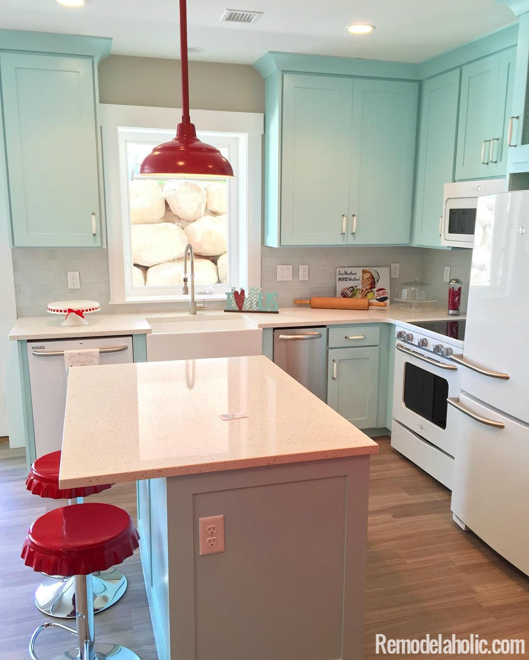 Super cute retro kitchen with light blue cabinets and red fixtures love it
