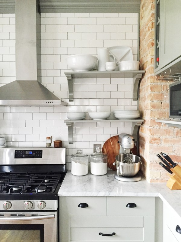 Stunning kitchen renovation, with an exposed brick wall, open shelving, and IKEA cabinets. By Carpendaughter on Remodelaholic.com