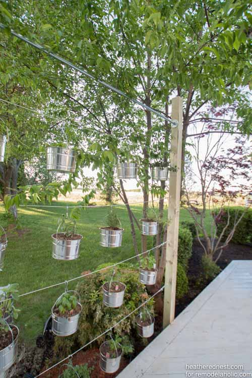 This suspended vertical garden is a great weekend DIY! Perfect for an herb garden or some beautiful flowers, and the kids could plant their own seeds in the lower rows. Tutorial from The Heathered Nest on @Remodelaholic.