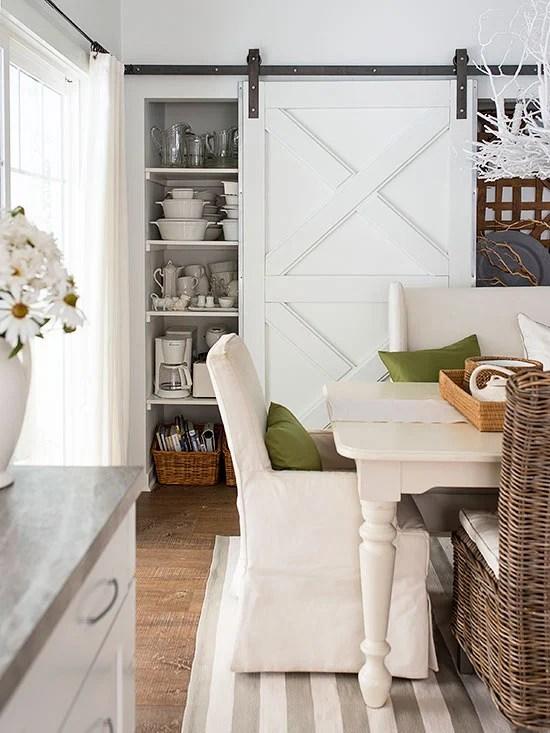 farmhouse dining room in neutrals with a sliding barn door via BHG