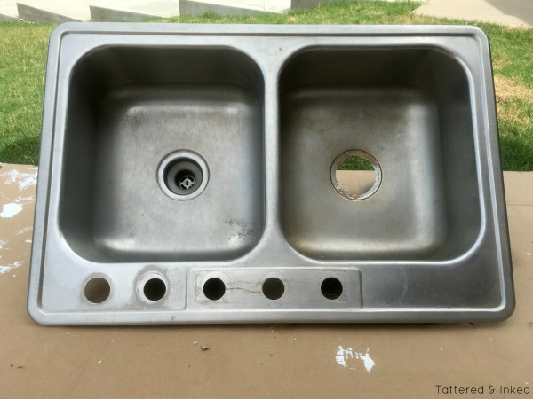 Reuse a double basin kitchen sink as a kids' sand and water table by Tattered and Inked featured on @Remodelaholic