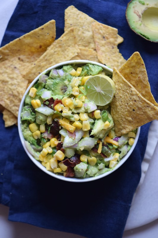 Need a yummy appetizer to bring to a party? Try this delicious bacon corn guacamole recipe via remodelaholic.com