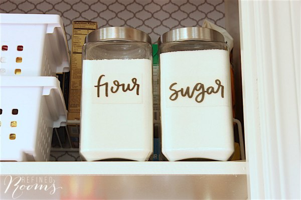 9 Glass Storage Jars With Clear Acrylic Printed Stickers For Use In Pantry Organization, By Refined Rooms Featured On @Remodelaholic