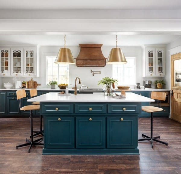 Fixer Upper Plain Jane House Kitchen: Modern farmhouse kitchen with white cabinets with the peacock blue island and gold pendants.