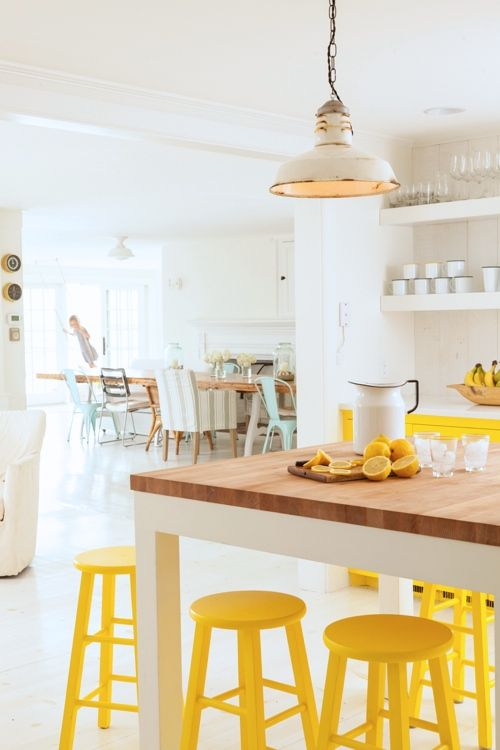 Neutral white with sunny yellow kitchen accents, cabinets, bar stools via Style Carrot | Yellow Kitchen Inspiration #Remodelaholic