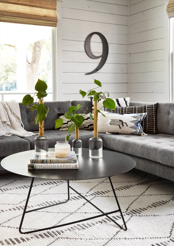 Get This Look: Fixer Upper Living Room from The Americana House | Recreate the iconic Joanna Gaines modern farmhouse chic style from the shiplap and neutral area rug to the chandelier and mid-century sofa with these tips, decorating picks, and DIY tutorials #getthislook #remodelaholic #fixerupper #modernfarmhouse