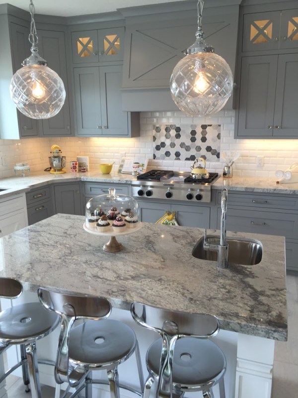 Get This Look: Beautiful gray kitchen cabinets with marble countertop, white kitchen island, and hanging globe pendants. Tips and product sources at #remodelaholic