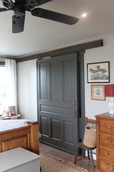 Bedroom With Large Grey Barn Door And Wooden Bed And Dresser Set