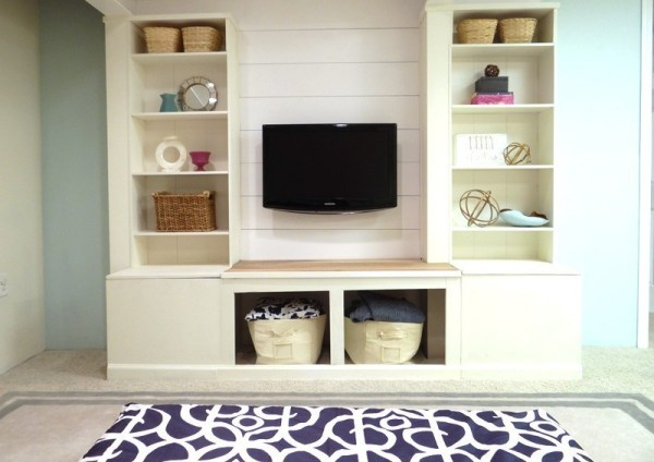 Built In White Shelves And Media Wall Unit With Storage Squares Against Blue Wall With Blue Rug