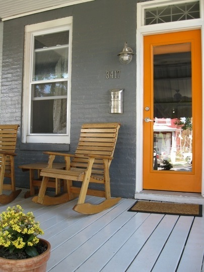 Grey Wooden Porch With Grey Painte Bricks And Orange Door With Long Glass Center And Wooden Rocking Chairs