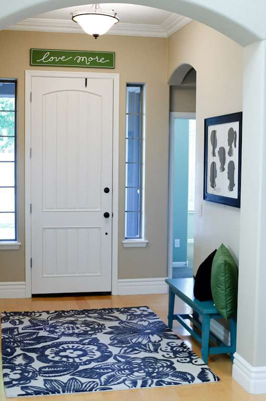 Entryway With Archway, Grey Walls, Wooden Flooring, Blue Floral Rug In Front Of White Door, Blue Bench And Love More Sign Above Door