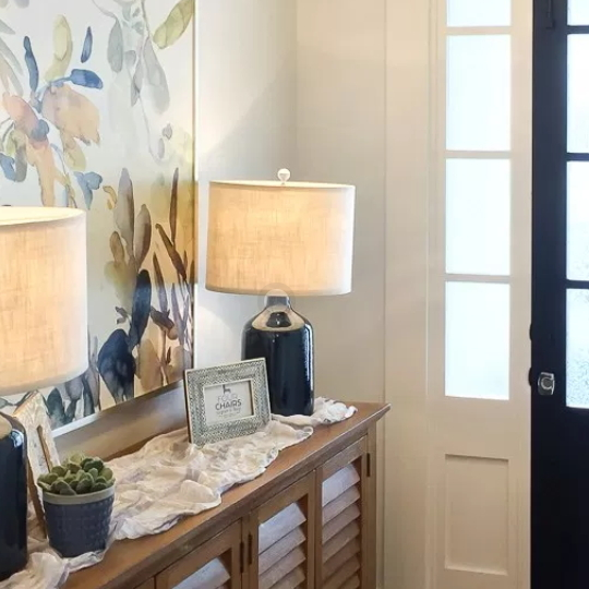 Entryway With Brown Long Table And Lace Table Runner And Navy Lamps And Flower Pots