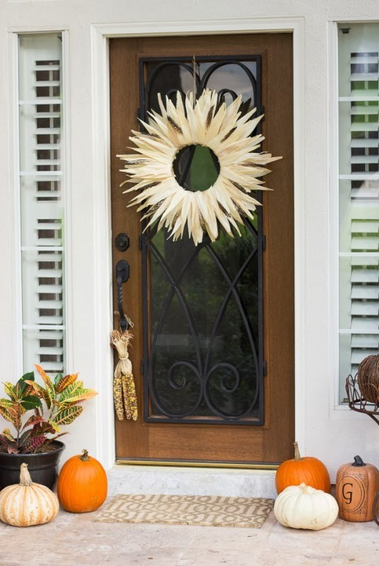 Corn Husk Wreath In Circle With Open Center On A Wooden Door With Glass Center And Fall Porch With Pumpkins And Hanging Corn Cobs
