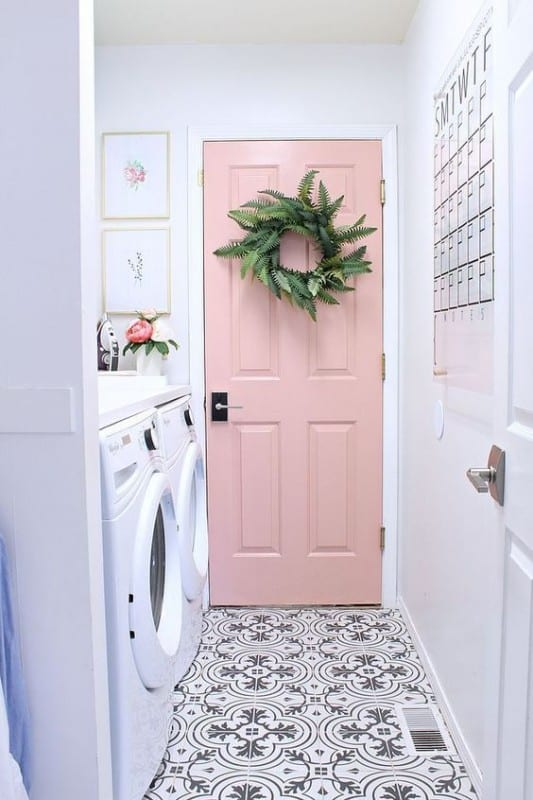 Grey And White Patterned Floor Of Long Narrow Laundry Room, White Front Load Washer And Dryer On The Side, Calendar On Opposite Wall, Pale Pink Door With Greenery Wreath At End