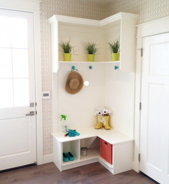 Tall White Corner Shelf With Hooks And Cubbys, Lit With Colorful Flower Pots And Greenery, Rainboots, Garden Gloves And A Wicker Basket