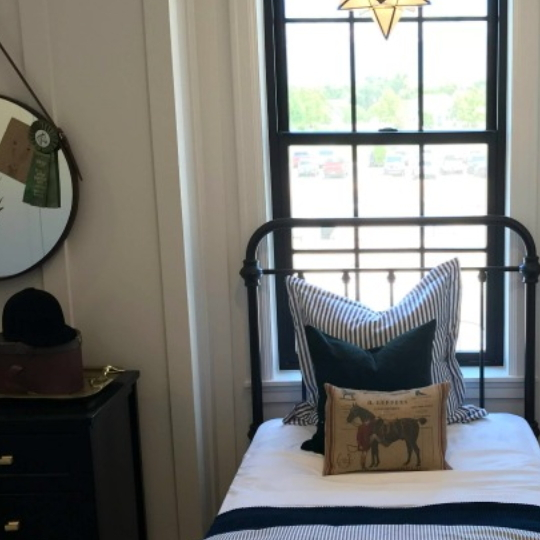 Farmhouse Themed Boys Bedroom With Metal Bedframe And Striped Bedspread And Pillow With Horse Pillow And White Accented Walls