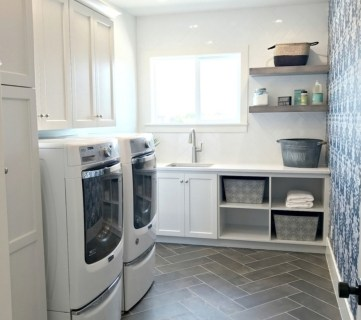 Grey Herringbone Tile Floor With Washer And Dryer And Blue Floral Wallpaper Accent Wall And Natural Wood Shelves