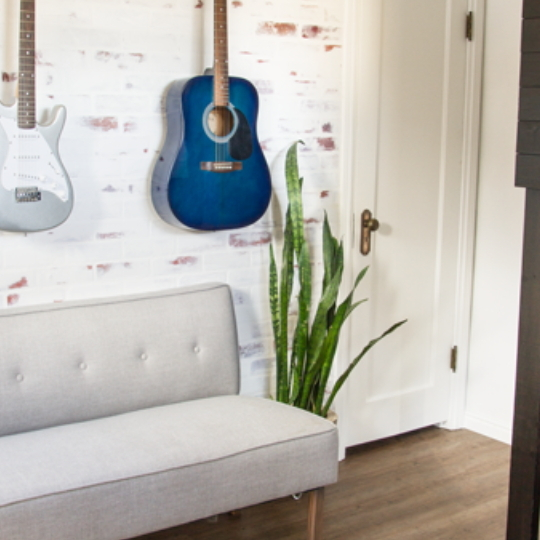 Red Brick Wall Painted White With Red Accents Coming Through Guitars Hanging On Wall, Grey Couch And Green Plant