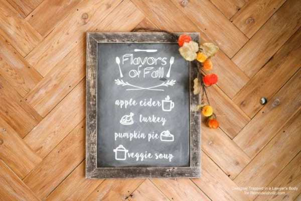 Herringbone Wooden Floor With A Reusable Faux Chalkboard Sign With Flavors Of Fall On It Showing Apple Cider, Turkey, Pumplin Pie And Veggie Soup
