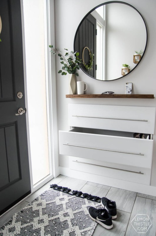 Grey And White Entryway With Drawers Into The Wall, Stainless Steel Bar Handles And Circular Mirror And Wooden Shelf