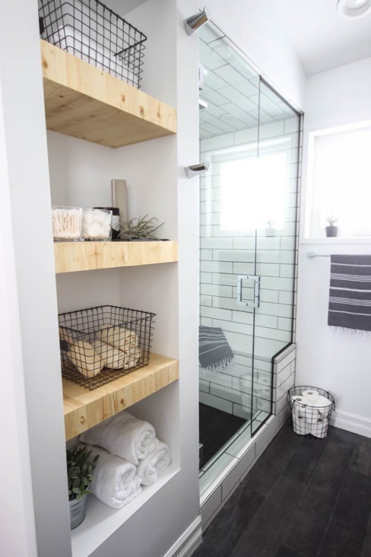 White Bathroom With Tiled Glass Shower And Wooden Shelves With Metal Baskets