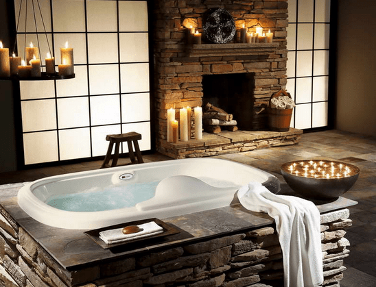 bathtub surrounded by natural stones and design candles