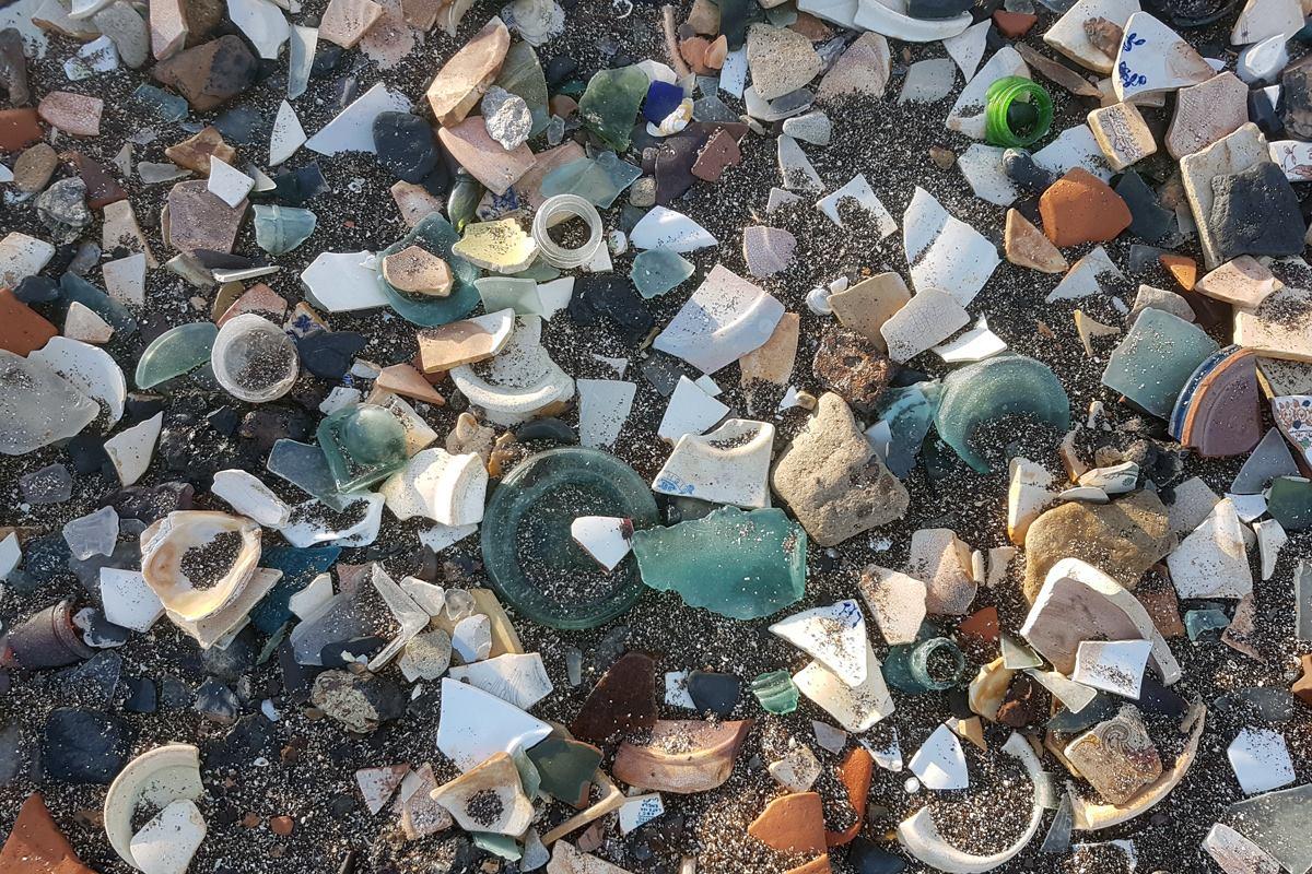 Broken crockery and bottles cover a beach