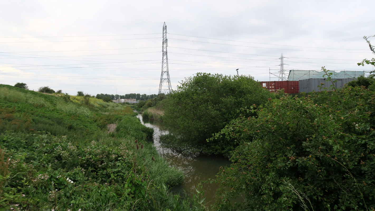 The river Gores flows between green banks towards a large, distant pylon. More pylons can be seen on the horizon