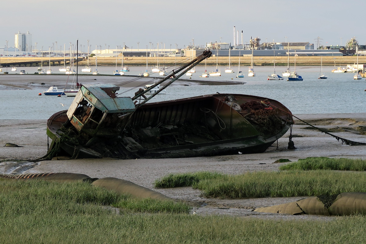 A rusting, sixty foot long barge with a crane rests at an angle on the mud at Queenborough