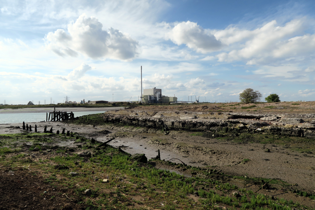 The old wharf at Elmley Cement Works. One side is broken concrete, the other wooden. The dock is full of mud.