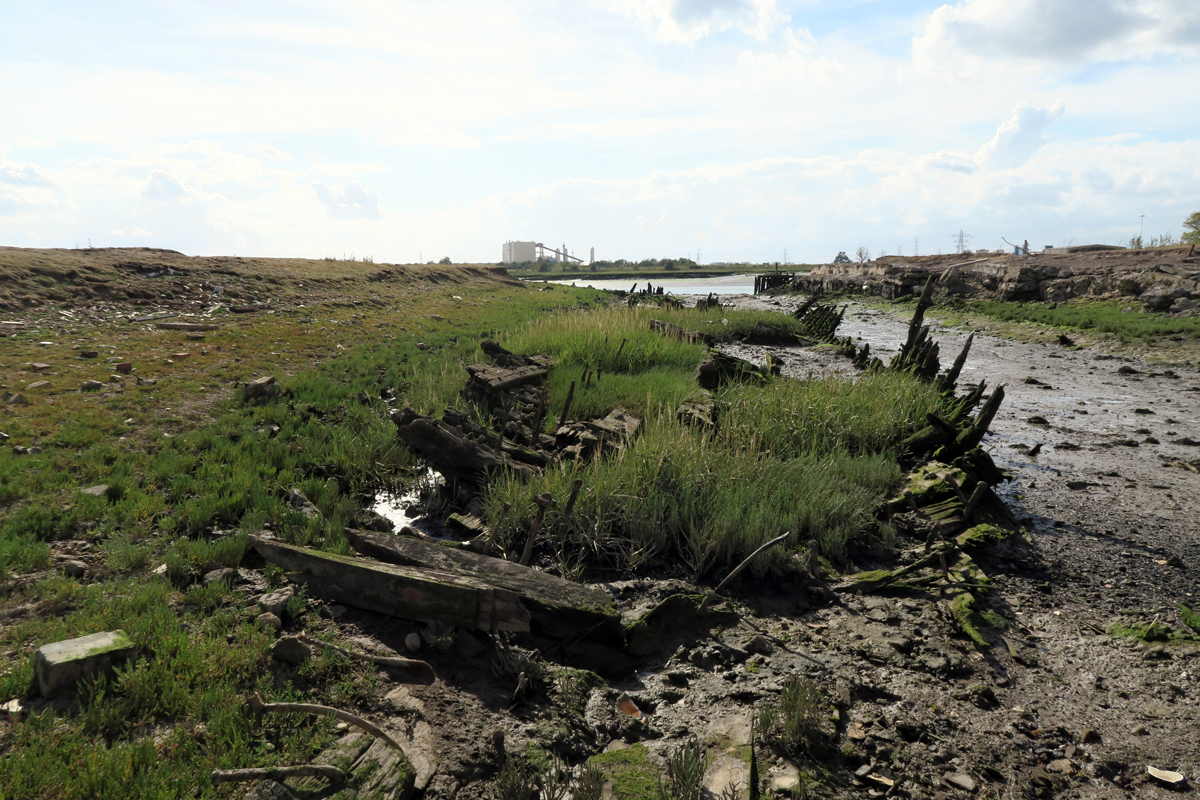 The wharf's mud-choked dock contains the skeletal remains of a wooden barge