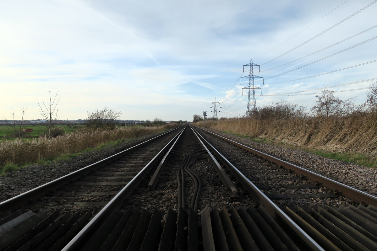 Looking along railway tracks. A flat landscape under a light blue sky. A line of tall electricity pylons to the right.