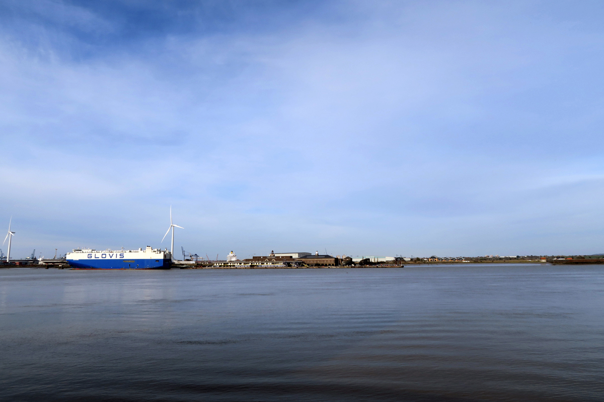 The view from Gravesend, looking across a blue, calm Thames towards Tilbury on the far bank. flat