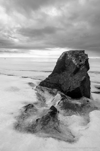 "A rock sticks out of the ice near Stokksnes. Nikon D810 24 mm (24.0 mm ƒ/1.4) 1/30"" ƒ/13 ISO 64"