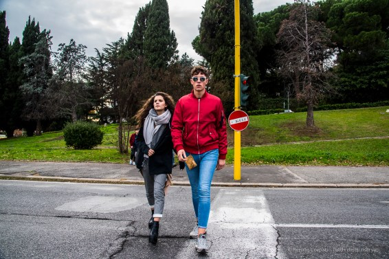 Two young adults crossing the Cristoforo Colombo near the Pala EUR. Nikon D810, 27 mm (24-120.0 mm ƒ/4) 1/160 ƒ/8 ISO 500