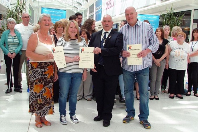 Caption: Caring for the carers – Renfrewshire Depute Provost John Caldwell, third from left, presents certificates to three of the carers, Anne Denholm, left, Brenda Duncanson and Mark McCabe at the intu Braehead mall.