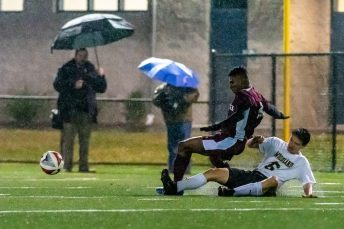 WATERBURY, CT. 07 November 2019-110719BS576 - Woodland's Sean Swanson (6) slides on the wet ground knocking the ball away from Naugatuck's Chris Akinduro (9), during the NVL Boys Soccer final between Naugatuck and Woodland at Municipal Stadium in Waterbury on Thursday. The Naugatuck boys soccer team are the 2019 NVL Champions after beating Woodland 2-1. Bill Shettle Republican-American