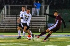 WATERBURY, CT. 07 November 2019-110719BS576 - Naugatuck's Lucas Silva (7), right, shoots and scores a goal with Woodland's Jack Schwarz (13) defending, during the NVL Boys Soccer final between Naugatuck and Woodland at Municipal Stadium in Waterbury on Thursday. The Naugatuck boys soccer team are the 2019 NVL Champions after beating Woodland 2-1. Bill Shettle Republican-American