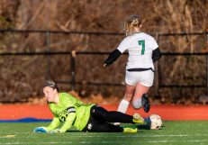 WATERBURY, CT. 16 November 2019-111619BS487 - Holy Cross goalkeeper Tori Schaffner (24) comes out and makes a save on Coventry's Natalie Neal (7) preserving her shutout, during a Class S quarterfinal match between Coventry and Holy Cross at Crosby High School in Waterbury on Saturday. Holy Cross beat Coventry 3-0 and advances to the Class S semi-finals next week. Bill Shettle Republican-American