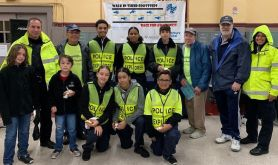 Police Explorers along with Officer Michael Chiarella, far left rear row, assisted the walkers on their route. Also standing in the rear: Edwin Rodriguez, second from left, director of development and community relations, Gary Beaulieu, second from right, executive director, and Deacon George Pettinico, third from right, event coordinator.