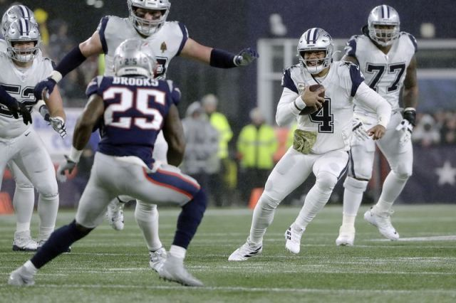 Dallas Cowboys quarterback Dak Prescott, right, carries the ball as New England Patriots defensive back Terrence Brooks, left, gives chase in the first half of an NFL football game, Sunday, Nov. 24, 2019, in Foxborough, Mass. (AP Photo/Steven Senne)