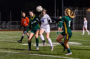 NAUGATUCK, CT. 20 November 2019-112019BS863 - Litchfield's Ella Demers (16) heads the ball in front of Holy Cross' Devon Bushka (13) with Holy Cross' Juliana Dane (19) helping out with defense, during the Girls Soccer Class S semifinal match between Litchfield and Holy Cross at Naugatuck High School on Wednesday. Holy Cross beat Litchfield 3-1 and advances to the Class S final this Saturday. Bill Shettle Republican-American