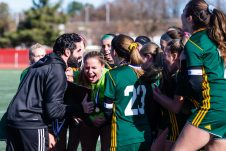 New Britain, CT. 23 November 2019-112319BS975 - Holy Cross head coach Phil Mongelluzzo, left, holds the Class S State trophy as he and all the girls celebrate together after Holy Cross beat Old Lyme 1-0 in the Class S Girls Soccer final at Willowbrook Park in New Britain on Saturday. Bill Shettle Republican-American