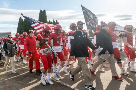 CHESHIRE, CT. 28 November 2019-112819BS1255 - Cheshire Football head coach Don Drust, center, leads the Cheshire football team out to the field before a SCC game and the annual Cheshire vs Southington Thanksgiving game called the Apple Valley Classic at Cheshire High School on Thursday. Southington won 21-20 in double overtime. Bill Shettle Republican-American