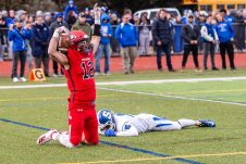 CHESHIRE, CT. 28 November 2019-112819BS1266 - Cheshire's Nicholas DiDomizio (12) celebrates his touchdown in the end zone as Southington's John Carreiro (25) looks on from the ground, during a SCC game and the annual Cheshire vs Southington Thanksgiving game called the Apple Valley Classic at Cheshire High School on Thursday. Southington won 21-20 in double overtime. Bill Shettle Republican-American