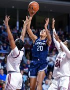 Connecticut forward Olivia Nelson-Ododa (20) goes up for a shot over Temple guard Rayniah Walker, left, and forward Shantay Taylor (24) during the second half of an NCAA college basketball game Sunday, Nov. 17, 2019, in Philadelphia. Connecticut won 83-54. (AP Photo/Laurence Kesterson)