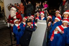 WATERBURY, CT. 08 December 2019-120819BS18 - Waterbury detective Andrea Saunders, bottom left, with help from the PAL Children's Chorus, all react after hitting the switch to illuminate the city green with Christmas lights, during the the annual lighting of the Christmas Tree and surrounding lights on the City Green to help launch the Holiday Season in downtown Waterbury on Sunday. The lighting ceremony was pushed backed on week due to the snowstorm last weekend. Bill Shettle Republican-American