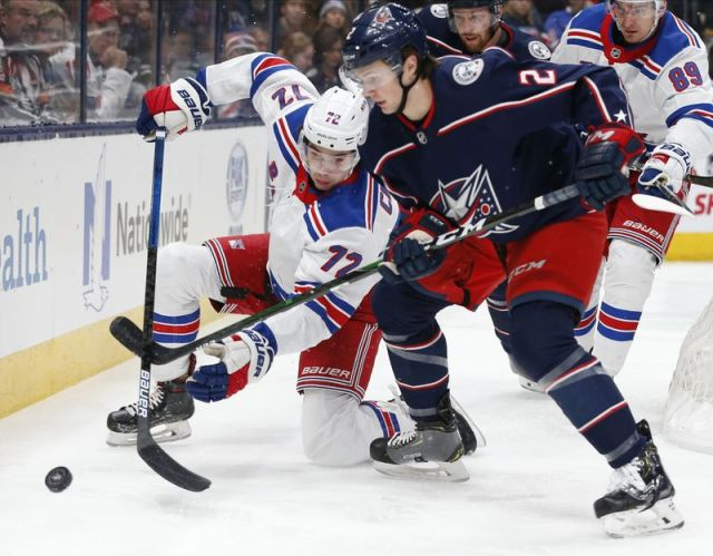 New York Rangers' Filip Chytil, left, of the Czech Republic, and Columbus Blue Jackets' Andrew Peeke fight for the puck during the first period of an NHL hockey game Thursday, Dec. 5, 2019, in Columbus, Ohio. (AP Photo/Jay LaPrete)